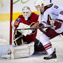 Calgary Flames' goalie Karri Ramo, left, from Finland, takes a high sticking penalty on Phoenix Coyotes' David Moss during third period NHL action Wednesday, Dec. 4, 2013 in Calgary, Alberta The Associated Press