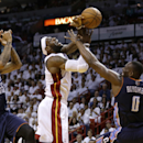 Miami Heat's LeBron James, center, is fouled by Charlotte Bobcats' Bismack Biyombo (0) as Bobcats' Chris Douglas-Roberts (55) looks on during the first half in Game 1 of an opening-round NBA basketball playoff series on Sunday, April 20, 2014, in Miami Th