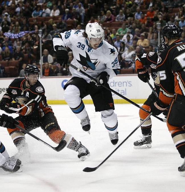 San Jose Sharks' Logan Couture, center, jumps out of the way as Jason Demers, left, tries to score against Anaheim Ducks goalie John Gibson during the first period of an NHL hockey game Wednesday, April 9, 2014, in Anaheim, Calif