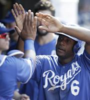 Kansas City Royals' Lorenzo Cain is congratulated by teammates after scoring on an RBI-single by Mike Moustakas in the eighth inning of a baseball game, Wednesday, Sept. 11, 2013, in Cleveland. (AP Photo/Tony Dejak)