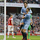 Manchester City's David Silva, top, celebrates scoring a goal with teammate Edin Dzeko during the English Premier League soccer match between Arsenal and Manchester City at the Emirates stadium in London, Saturday, March 29, 2014