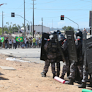 Riot police block protesters near the Castelao stadium in Fortaleza, Brazil, Wednesday, June 19, 2013. Protesters cut off the main access road to the stadium where Brazil will play Mexico in the Confederations Cup soccer tournament later Wednesday. Beginning as protests against bus fare hikes, the demonstrations have quickly ballooned to include broad middle-class outrage over the failure of governments to provide basic services and ensure public safety. (AP Photo/Andre Penner)