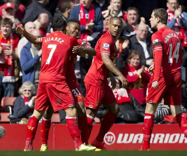 Liverpool's Raheem Sterling, second left, celebrates with teammates after scoring against Manchester City durig their English Premier League soccer match at Anfield Stadium, Liverpool, England, Sunday April 13, 2014