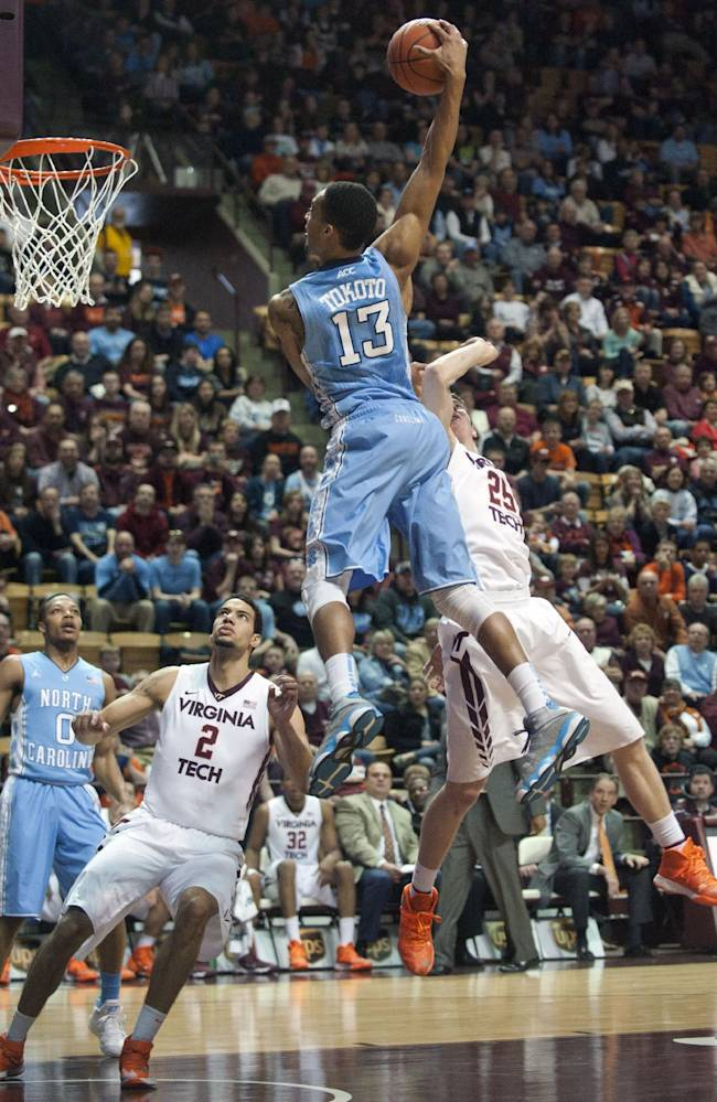 North Carolina's J.P. Tokoto goes up for a slam dunk against Virginia Tech's Will Johnson (25) and Joey van Zegeren (2)  during the first half of an NCAA college basketball game,  Saturday, March 1, 2014, in Blacksburg, Va