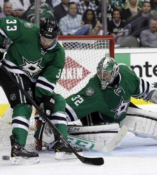 Dallas Stars' Alex Goligoski (33) helps goalie Kari Lehtonen (32) of Finland clear the puck away from the net during the second period of Game 3 of a first-round NHL hockey Stanley Cup playoff series game against the Anaheim Ducks, Monday, April 21, 2014, in Dallas
