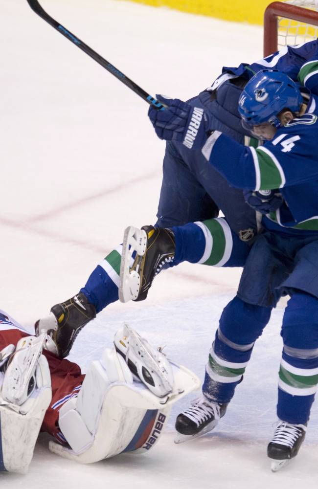 Vancouver Canucks defenseman Alexander Edler (23) crashes into teammate Alex Burrows after jumping over New York Rangers goalie Henrik Lundqvist (30) during the second period of NHL action in Vancouver, British Columbia, Tuesday, April 1, 2014