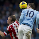 Manchester City's Edin Dzeko, right, fights for the ball against Stoke's Glenn Whelan during their English Premier League soccer match at the Etihad Stadium, Manchester, England, Saturday Feb. 22, 2014
