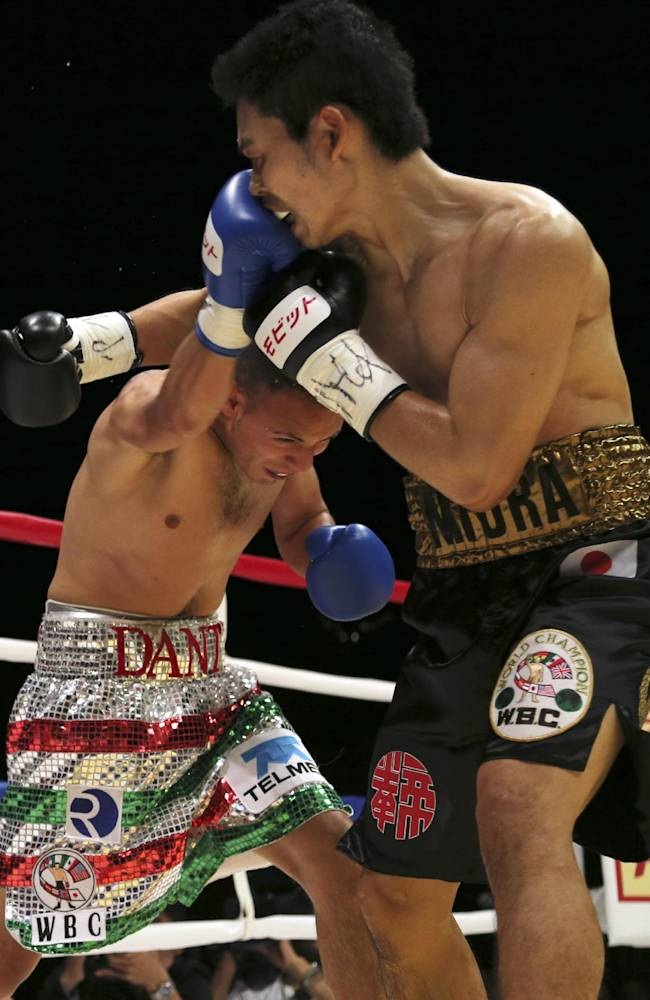 Japanese champion Takashi Miura, right, and Mexican challenger Dante Jardon exchange punches in the first round of their WBC super featherweight title bout in Tokyo Tuesday, Dec. 31, 2013. Miura defended his title by a technical knockout in the ninth round