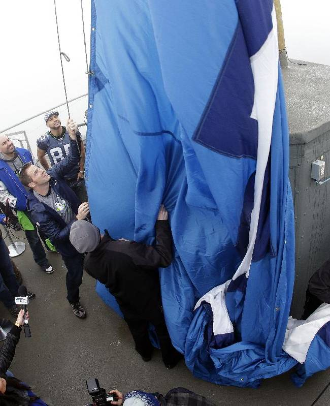 In this photograph taken with a fisheye lens, former Seattle Seahawks defensive tackle Craig Terrill, center-left, helps raise a Seahawks' 12th Man flag on the roof of the Space Needle, Friday, Jan. 17, 2014, in Seattle. The Seahawks will play the San Francisco 49ers Sunday in the NFC championship in Seattle