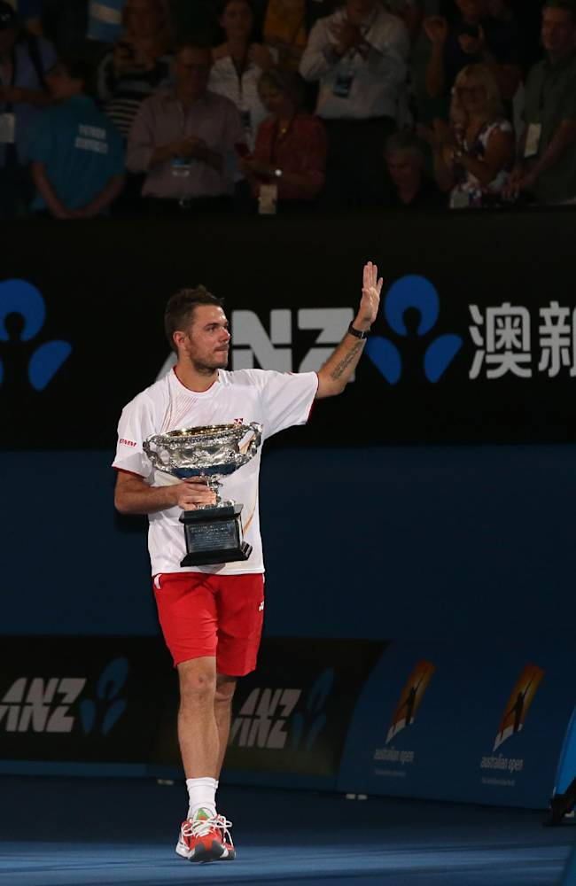 Stanislas Wawrinka of Switzerland walks around the court with the trophy after defeating Rafael Nadal of Spain in the men's singles final at the Australian Open tennis championship in Melbourne, Australia, Sunday, Jan. 26, 2014