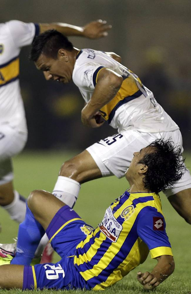 Andres Eliseo Chavez of Argentina's Boca Juniors, top, fights for the ball with Arnaldo Pereira of Paraguay's Deportivo Capiata, on the ground, during a Copa Sudamericana soccer match in Asuncion, Paraguay, Thursday, Oct. 23, 2014
