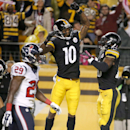 Pittsburgh Steelers wide receiver Martavis Bryant (10) celebrates with running back Le'Veon Bell (26) after making a touchdown catch as Houston Texans defensive back Andre Hal (29) walks by in the second quarter of the NFL football game, Monday, Oct. 20, 2014 in Pittsburgh. (AP Photo/Gene J. Puskar)