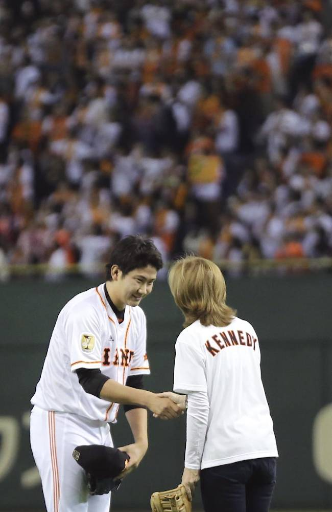 U.S. Ambassador to Japan Caroline Kennedy is greeted by Yomiuri Giants starter Tomoyuki Sugano on the mound after her ceremonial first pitch before the Japan's Central League professional baseball opening game between the Yomiuri Giants and the Hanshin Tigers at Tokyo Dome in Tokyo, Friday, March 28, 2014