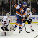 New York Islanders center Brock Nelson (29) leaps into the air with the puck between Chicago Blackhawks goalie Scott Darling (33) and defenseman Duncan Keith (2) in the second period of an NHL hockey game at Nassau Coliseum on Saturday, Dec. 13, 2014, in
