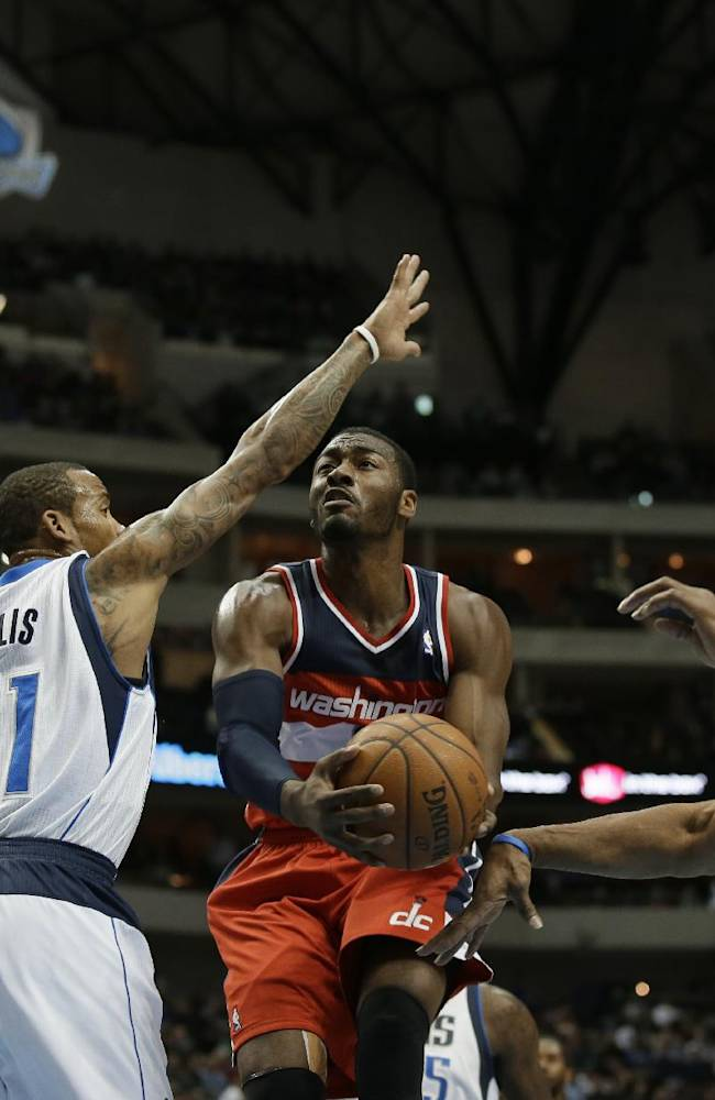 Washington Wizards guard John Wall (2) gets past Dallas Mavericks' Monta Ellis (11) and Vince Carter, right, for a shot attempt in the first half of an NBA basketball game, Tuesday, Nov. 12, 2013, in Dallas