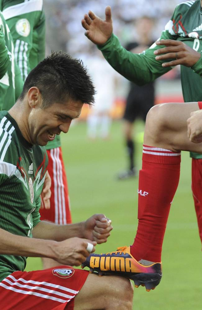 Mexico's Oribe Peralta performs to polish a shoe of teammate Miguel Layun after scoring a goal against New Zealand in their World Cup qualifying soccer match at Westpac Stadium in Wellington, New Zealand, Wednesday, Nov. 20, 2013