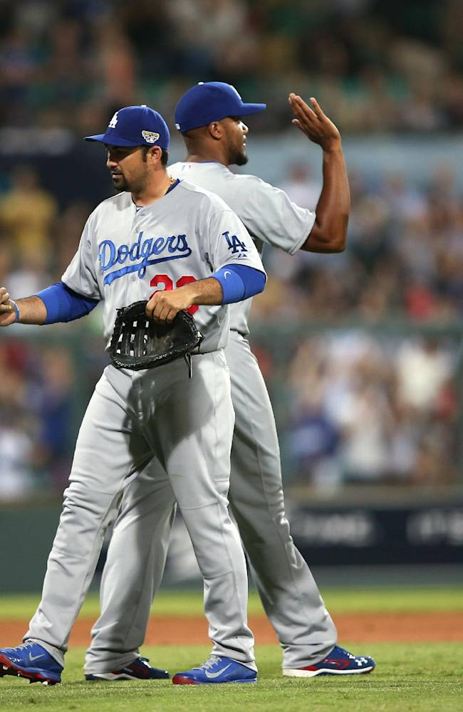 The Los Angeles Dodgers' A.J. Ellis, left, Adrian Gonzalez, second left, Kenley Jansen and Juan Uribe, right, celebrate their win in the Major League Baseball opening game between the Los Angeles Dodgers and Arizona Diamondbacks at the Sydney Cricket ground in Sydney, Saturday, March 22, 2014. The Dodgers won the game 3-1