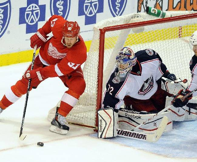 Detroit Red Wings right winger Johan Franzen, left, tries to work the puck in front of Columbus Blue Jacket goalie Sergei Bobrovsky during the third period of an NHL hockey game Tuesday, Oct. 15, 2013, in Detroit