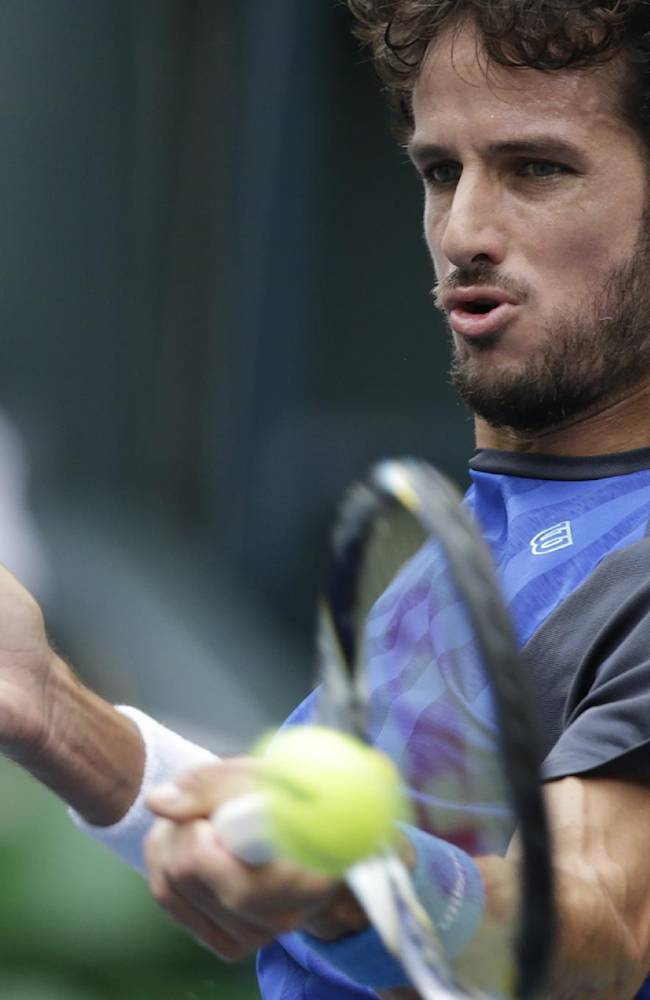 Feliciano Lopez of Spain returns the ball against Tatsuma Ito of Japan during their first round match at the Japan Open Tennis Championships in Tokyo, Tuesday, Oct. 1, 2013. Lopez won 4-6, 7-5, 6-3