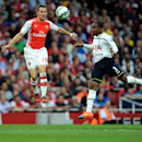 Arsenal's Aaron Ramsey and Tottenham Hotspur's Danny Rose vie for the ball during their English Premier League soccer match at the Emirates Stadium, London, Saturday, Sept. 27, 2014.