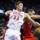 Detroit Pistons forward Jonas Jerebko (33), of Sweden, grabs a rebound away from Toronto Raptors center Jonas Valanciunas (17) in the first half of an NBA basketball game on Friday, March 29, 2013, in Auburn Hills, Mich. (AP Photo/Duane Burleson)