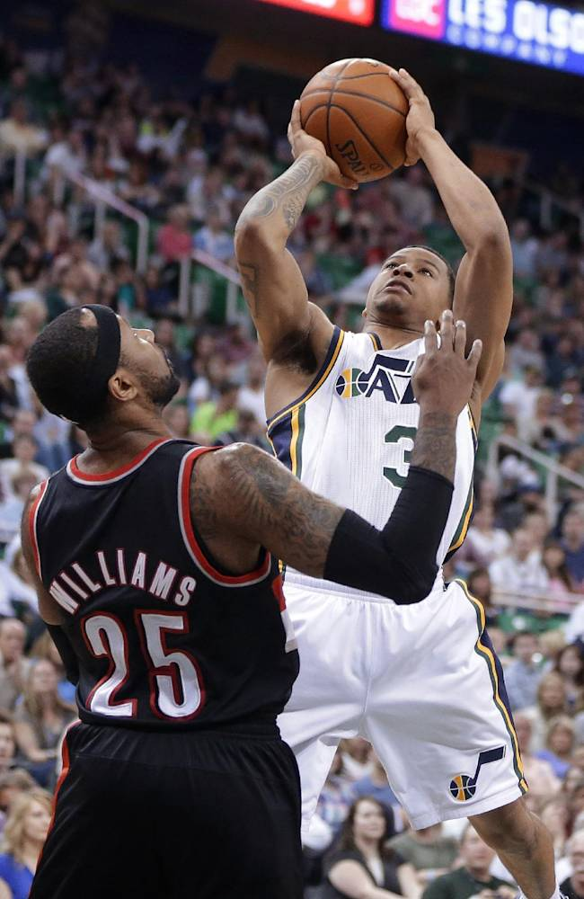 Utah Jazz's Trey Burke (3) shoots as Portland Trail Blazers' Mo Williams (25) defends during the second half of an NBA basketball game Friday, April 11, 2014, in Salt Lake City. The Trail Blazers won 111-99