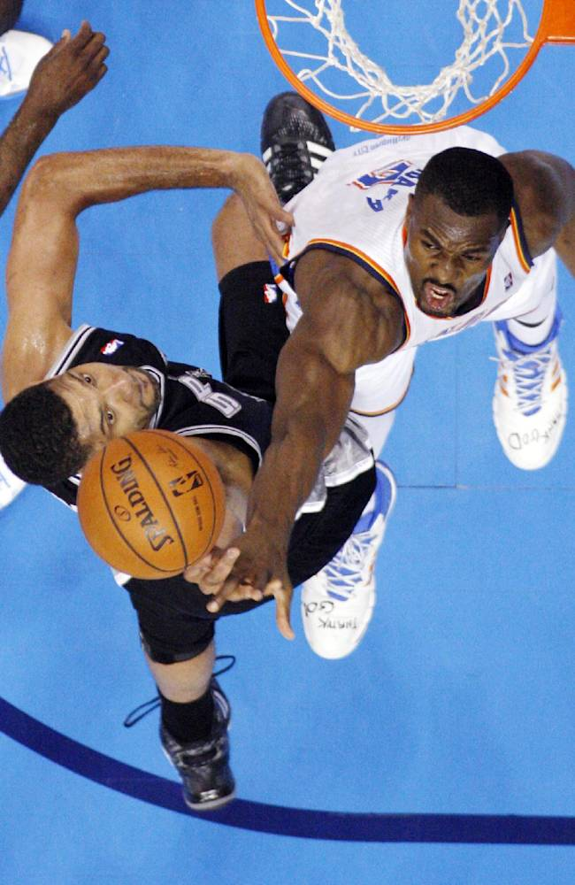 Oklahoma City Thunder forward Serge Ibaka, right, blocks a shot by San Antonio Spurs forward Tim Duncan in the first quarter of Game 3 of an NBA basketball playoff series in the Western Conference finals, Sunday, May 25, 2014, in Oklahoma City. Oklahoma City won 106-97