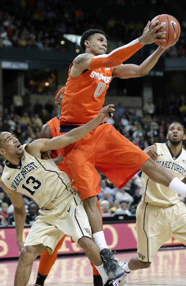 Syracuse's Michael Gbinije (0) pulls down a rebound over Wake Forest's Coron Williams (13) during the second half of an NCAA college basketball game in Winston-Salem, N.C., Wednesday, Jan. 29, 2014. Syracuse won 67-57