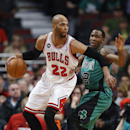 Chicago Bulls forward Taj Gibson, left, looks to pass the ball against Boston Celtics forward Chris Johnson, right, during the first half of an NBA basketball game in Chicago, Monday, March 31, 2014 The Associated Press