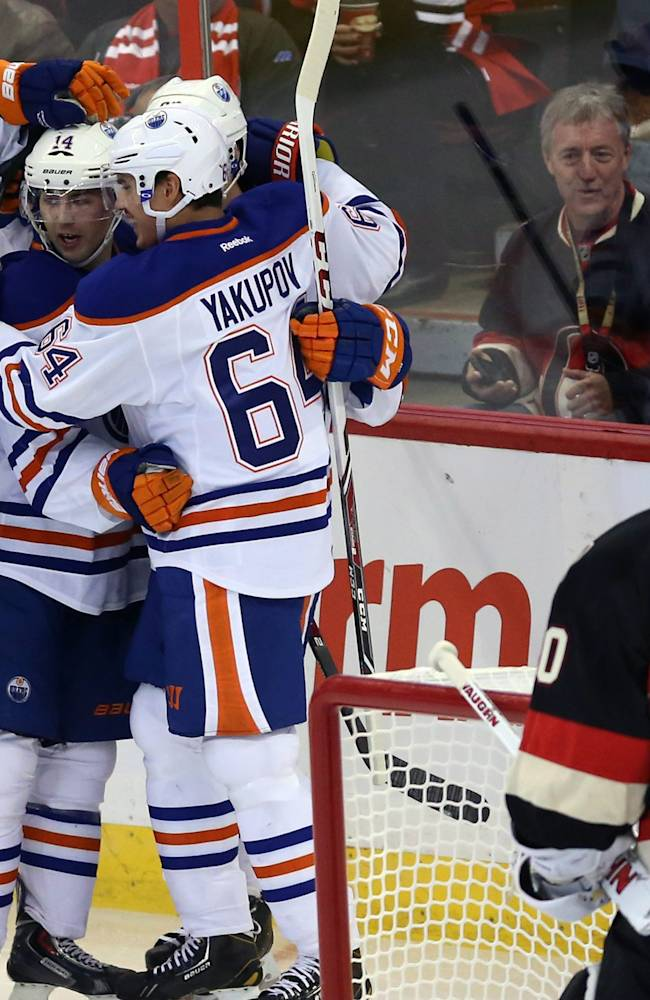 Edmonton Oilers' Jordan Eberle (14) celebrates his goal with teammates Nail Yakupov (64) and Andrew Ference (21) during the first period of an NHL hockey against the Ottawa Senators in Ottawa, Saturday, Oct. 19, 2013
