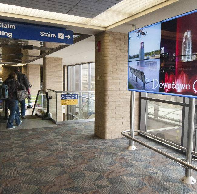 Air travelers walk past an information board Thursday, Jan. 23, 2014, at Eppley Airfield in Omaha, Neb. Unless Peyton Manning changes his habits, the Super Bowl-watching world will get to hear