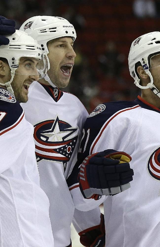 Columbus Blue Jacket's R.J. Umberger, center, celebrates his goal against the Carolina Hurricanes with Nick Foligno (71) and James Wisniewski (21) during the first period of an NHL hockey game in Raleigh, N.C., Monday, Jan. 27, 2014. Carolina won 3-2