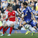 Arsenal's Jack Wilshere, left, passes the ball under pressure from Chelsea's Cesc Fabregas during their English Premier League soccer match between Chelsea and Arsenal at Stamford Bridge stadium in London Sunday, Oct. 5, 2014