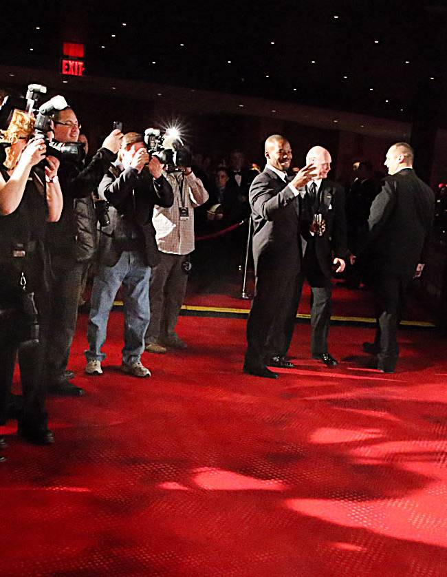 Denver Broncos quarterback Peyton Manning, right, poses for photographers on the red carpet in front of the Ovation Theater, Friday March 14 2014, at the Maxwell Football Awards at the Revel Casino and Hotel in Atlantic City, N.J