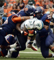 Tulane's Lazedrick Thompson (33) is tackled by from left, Syracuse's Cameron Lynch, Jay Bromley and Micah Robinson during an NCAA college football game at the Carrier Dome in Syracuse, N.Y., Saturday, Sept. 21, 2013. (AP Photo/Heather Ainsworth)