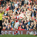 Referee Roger East shows a yellow card to Arsenal's Santi Cazorla, center, after reacting to an injury on Hull City's Ahmed Elmohamady, bottom right, during the English Premier League soccer match between Arsenal and Hull City at the Emirates stadium in L