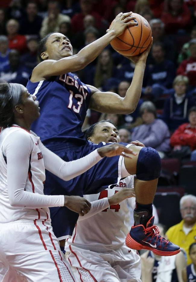 Connecticut guard Brianna Banks (13) takes a shot past Rutgers defenders, Betnijah Laney, right, and Kahleah Copper, left, during the second half of an NCAA women's college basketball game Sunday, Jan. 19, 2014, in Piscataway, N.J. Connecticut won 94-64