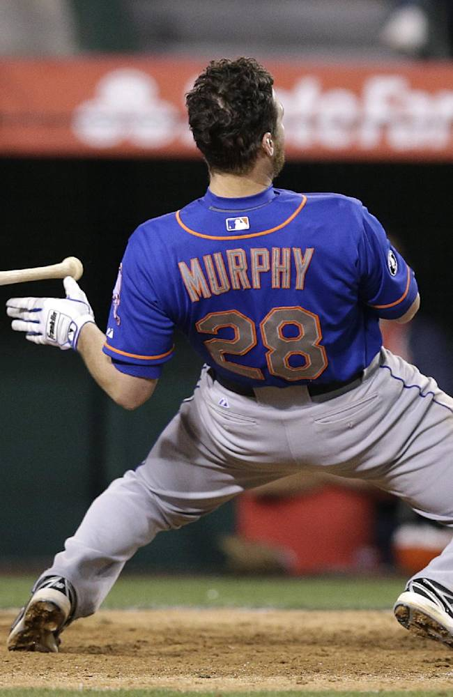 New York Mets' Daniel Murphy looses his helmet as he avoids a pitch during the 13th inning of a baseball game against the Los Angeles Angels on Saturday, April 12, 2014, in Anaheim, Calif
