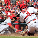 Cincinnati Reds' Billy Hamilton, left, scores ahead of the tag from St. Louis Cardinals catcher Yadier Molina on a sacrifice fly by Jay Bruce during the fifth inning of a baseball game Wednesday, April 9, 2014, in St. Louis The Associated Press