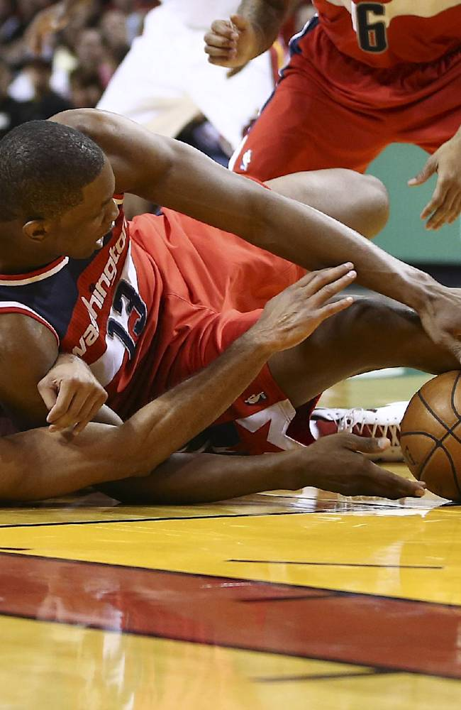 Miami Heat's Shane Battier (31) and Washington Wizards' Kevin Seraphin (13) battle for the ball during the first half of an NBA basketball game in Miami, Sunday, Nov. 3, 2013