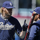 San Diego Padres starting pitcher Andrew Cashner, left, dicusses the particulars of hitting with teammate Ian Kennedy outside the batting cage during pregame activities before the opening game of Major League baseball in the United States between the Los