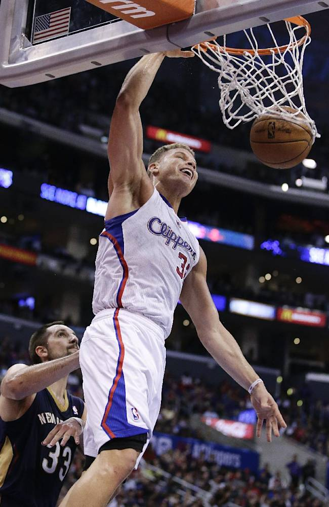 Los Angeles Clippers' Blake Griffin, center, dunks as New Orleans Pelicans' Ryan Anderson watches during the second half of an NBA basketball game on Wednesday, Dec. 18, 2013, in Los Angeles. The Clippers won 108-95