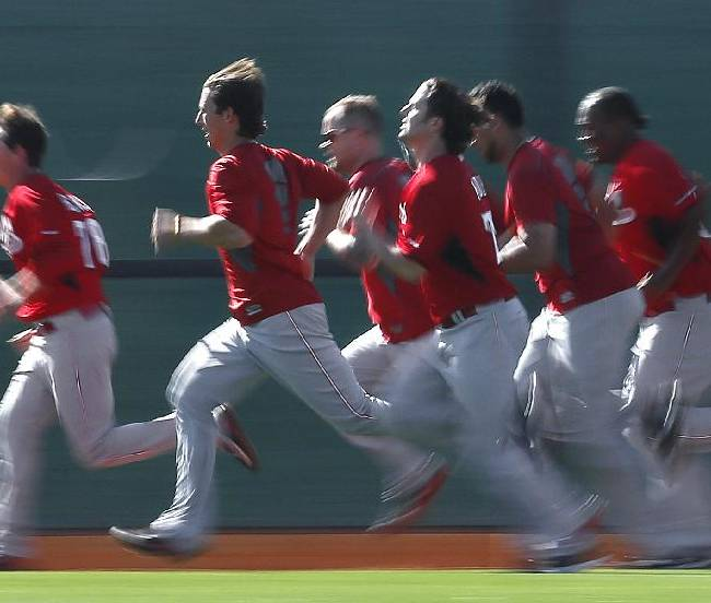 Cincinnati Reds players run during spring training baseball practice in Goodyear, Ariz., Saturday, Feb. 15, 2014
