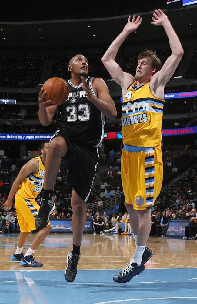 San Antonio Spurs forward Boris Diaw, left, of France, drives the lane for shot as Denver Nuggets forward Jan Vesely, of the Czech Republic, defends during the fourth quarter of the Spurs' 133-102 victory in an NBA basketball game in Denver on Friday, March 28, 2014