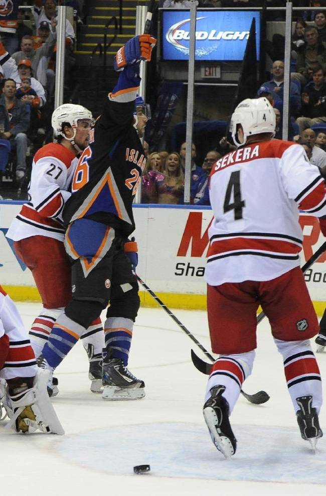 New York Islanders' Matt Moulson (26) celebrates his goal as Carolina Hurricanes goalie Cam Ward (30), Justin Faulk (27) and Andrej Sekera (4) react in the second period of an NHL hockey game on Saturday, Oct. 19, 2013, in Uniondale, N.Y