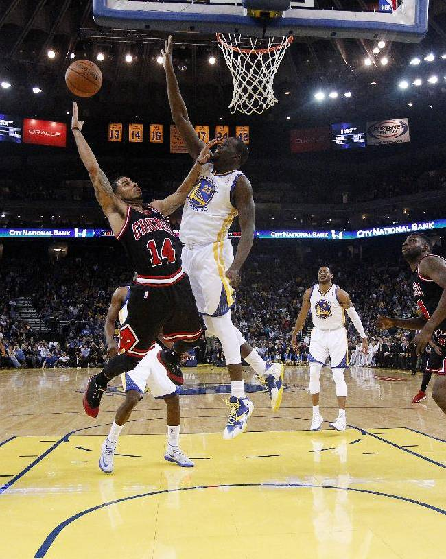 Chicago Bulls' D.J. Augustin (14) releases a shot as Golden State Warriors' Draymond Green (23) defends during the first half of an NBA basketball game Thursday, Feb. 6, 2014, in Oakland, Calif