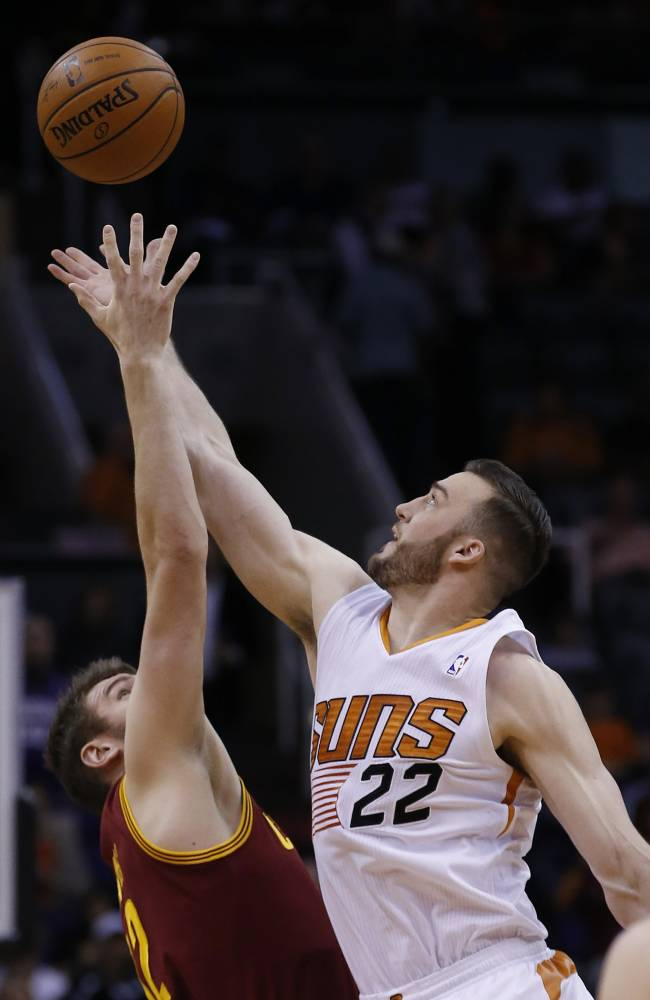 Phoenix Suns' Miles Plumlee (22) beats Cleveland Cavaliers' Spencer Hawes for a jump ball during the first half of an NBA basketball game on Wednesday, March 12, 2014, in Phoenix