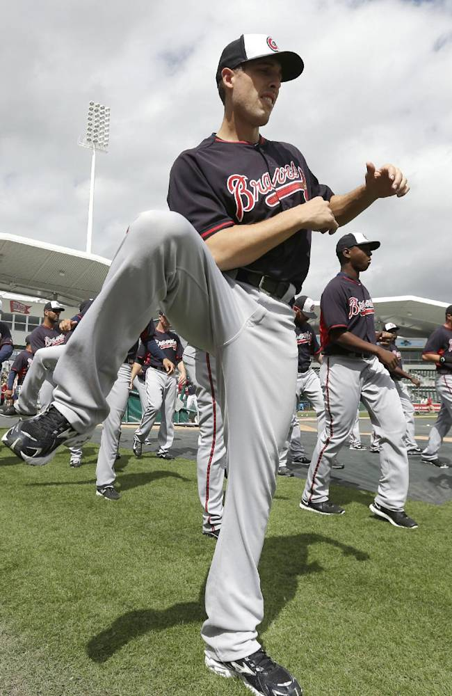 Atlanta Braves minor league player Mitch Atkins, front, warms up on the field with the Braves before an exhibition baseball game against the Boston Red Sox, Friday, March 7, 2014, in Fort, Myers, Fla