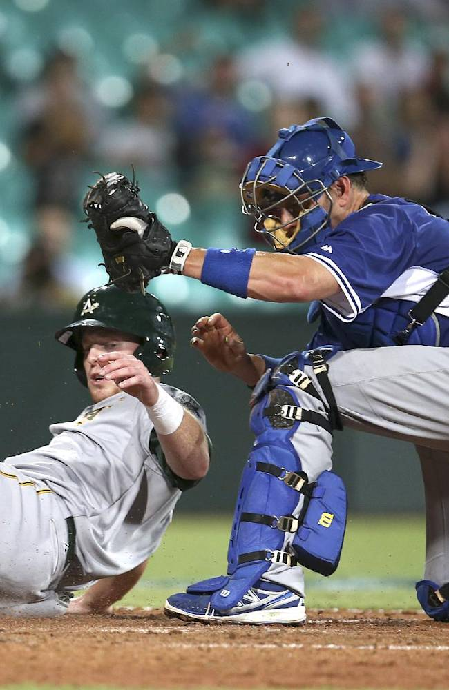 Team Australia's Mike Walker, left, is tagged out at home by Los Angeles Dodgers catcher A.J. Ellis during their exhibition baseball game at the Sydney Cricket Ground in Sydney, Thursday, March 20, 2014. The Arizona Diamondbacks and the Dodgers open the Major League Baseball regular season with games on Saturday and Sunday
