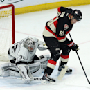 Los Angeles Kings goaltender Jonathan Quick (32) makes a stick save as he is screened by Ottawa Senators' Mark Stone (61) during the third period of an NHL hockey game, Thursday, Dec. 11, 2014 in Ottawa The Associated Press